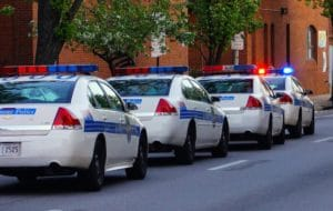 a line of parallel-parked police cars on the street