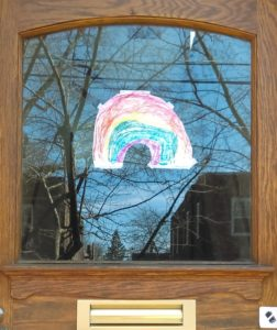 a wooden door with a window. on the window is taped a rainbow drawn in crayon