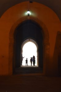 an arched doorway in Morocco with children's silhouettes lit up at the end of the hallway