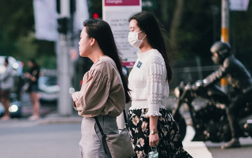 two women in masks wait to cross the street