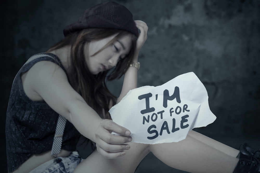 "a girl sits with her head bowed and hand on top of her head, holding a sign saying ""I'm not for sale"""