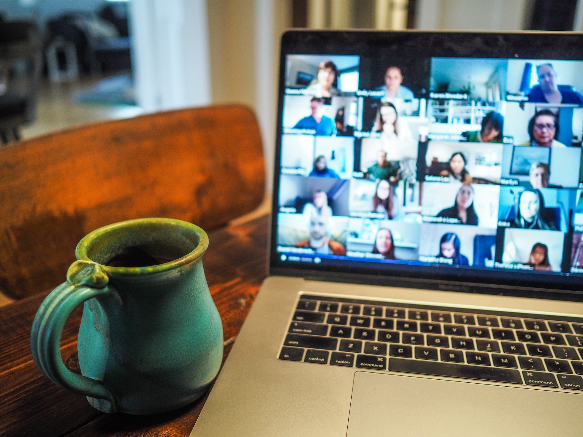 a laptop open to zoom with a mug sitting next to it