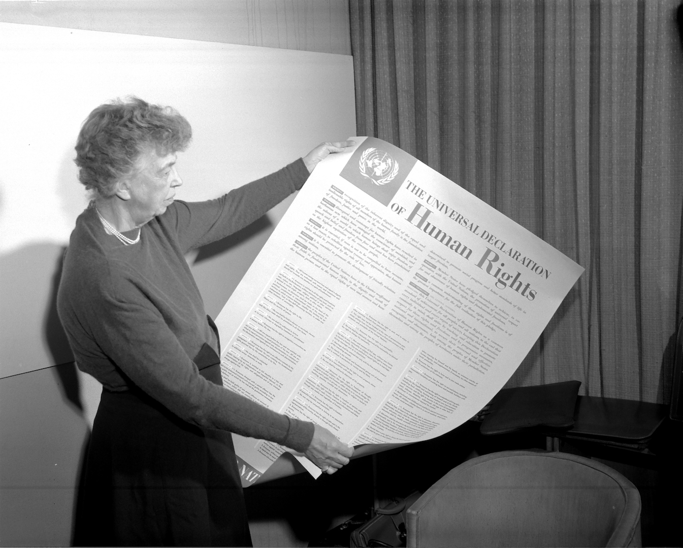 Mrs. Eleanor Roosevelt of the United States holding a Declaration of Human Rights poster in English.