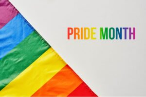 """rainbow flag and the words """"pride month"""" written in rainbow text"""