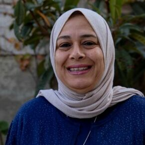 Hadeel Qazzaz smiles in a dark blue outfit with a light grey hijab