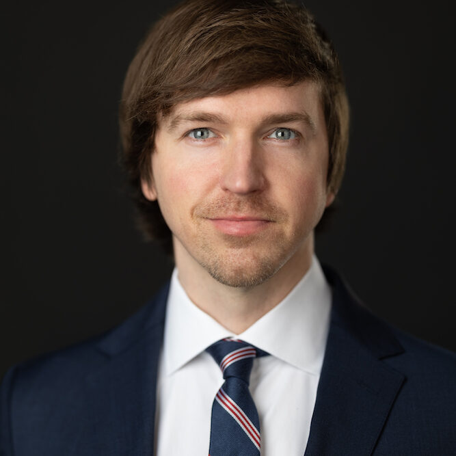 photo of a Phil Crehan, a white man with brown hair in a black suit
